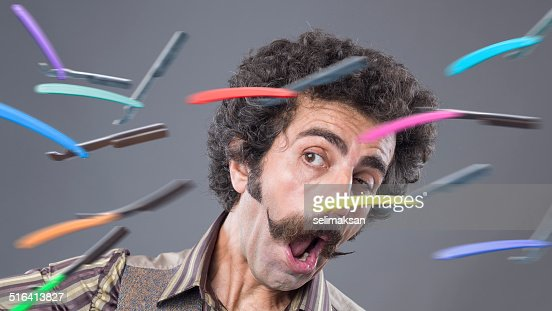 Man with handle bar mustache confronting flying razors