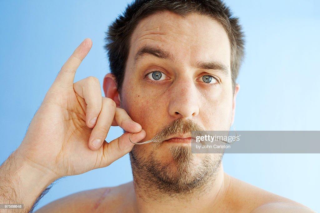 Man with handlebar mustache twirls one end : Stock Photo