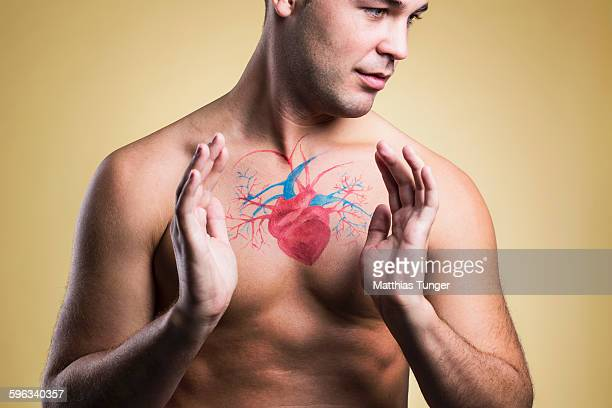 Man with hands around diagram of his heart