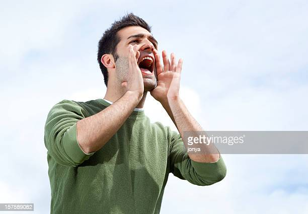 Man with hands around mouth to shout in distance