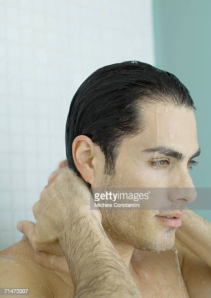 Man with hands behind neck in shower