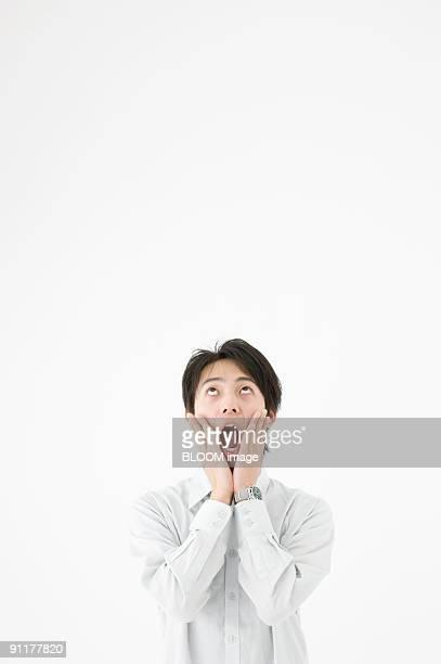 Man with hands on cheeks, looking upward