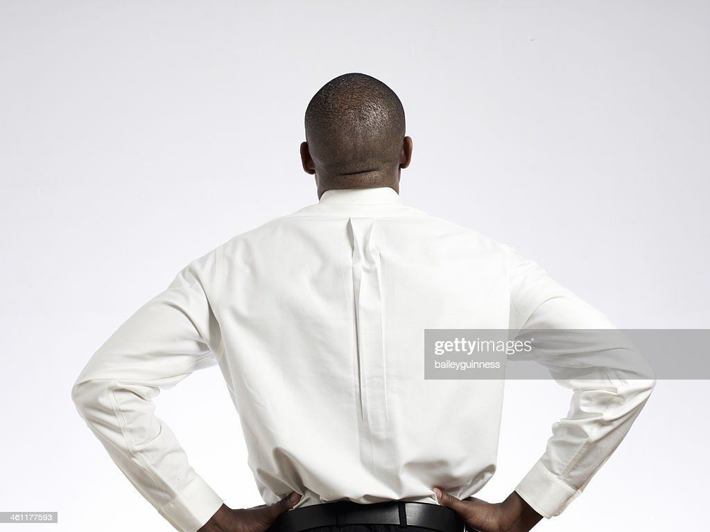 Man with hands on hips looking up