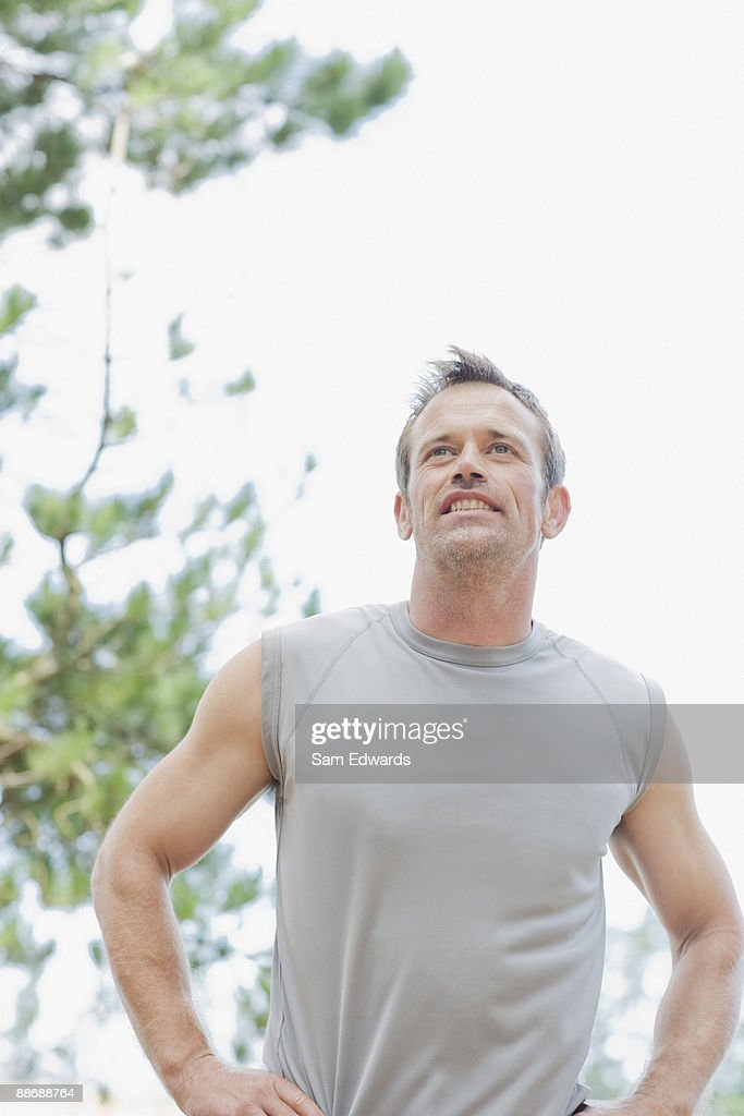 Man with hands on hips smiling : Stock Photo