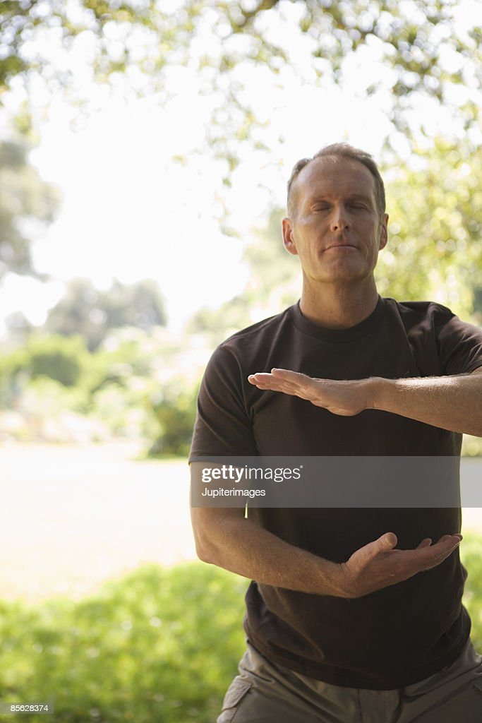 Man with hands surrounding his third chakra : Stock Photo