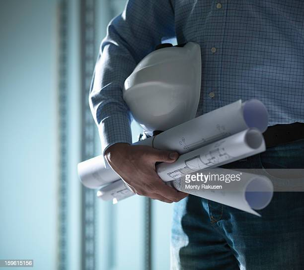 Man with hard hat under arm holding plans