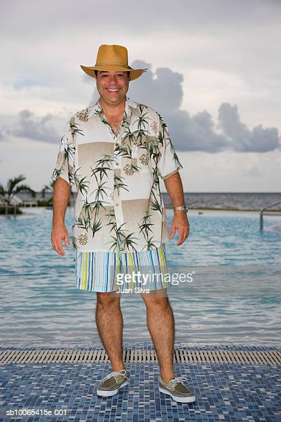 Man with hat and tropical shirt by pool, smiling portrait
