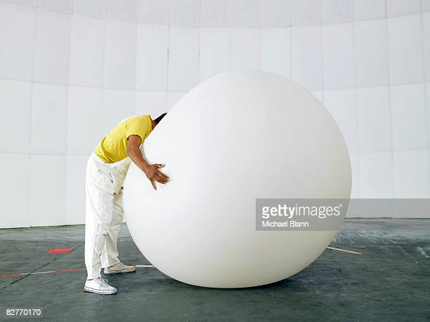 Man with head buried in huge weather balloon