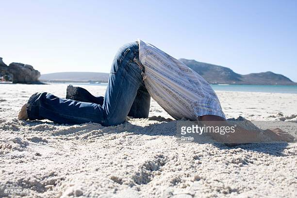 man with head buried in the sand