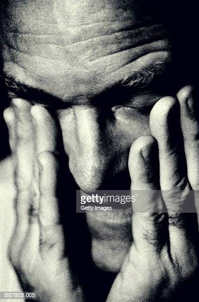 Man with head in hands, close-up (B&W)