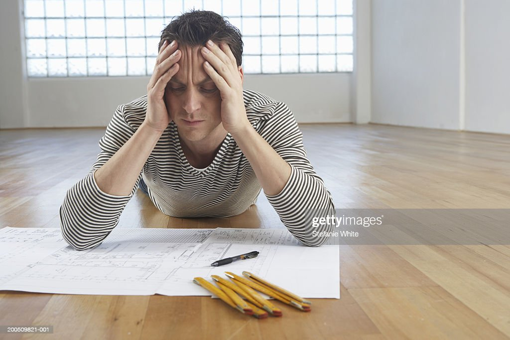 Man with head in hands, lying on floor with plans, eyes closed : Stock Photo