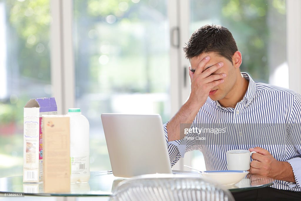 Man with head in hands, with laptop at breakfast