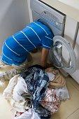 Man with head in washing machine