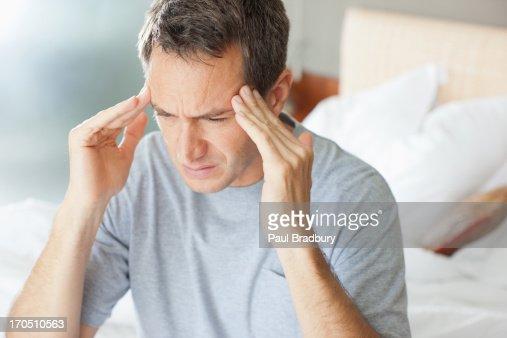 Man with headache rubbing forehead