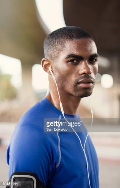 Man with headphones exercising on city street