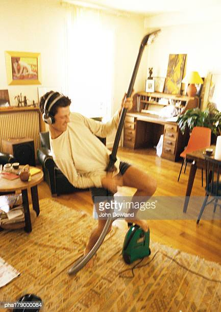 Man with headphones, holding vacuum cleaner, pretending to play guitar