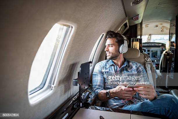 Man with headphones inside private jet airplane