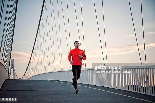 Man with headphones jogging on bridge