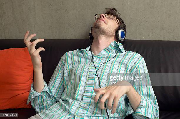 Man with headphones playing air guitar on the couch