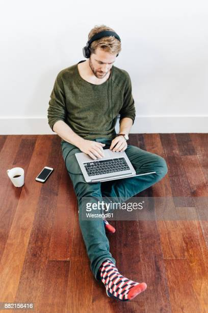 Man with headphones sitting on the floor at home using laptop