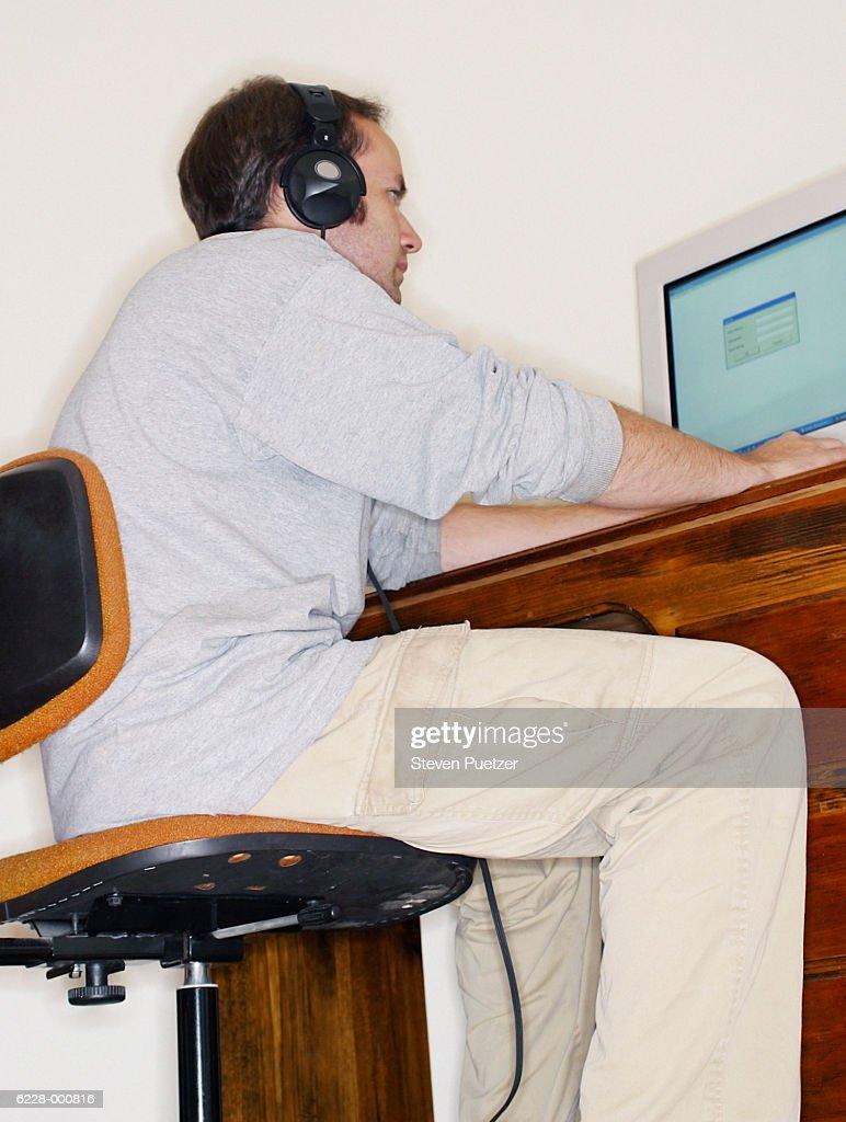 Man with headphones using computer : Stock Photo