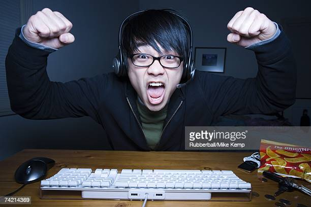 Man with headset making fists and sitting at keyboard
