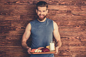 Handsome young bearded man in sportswear is holding a wooden tray with healthy food, looking at camera and smiling, on wooden background