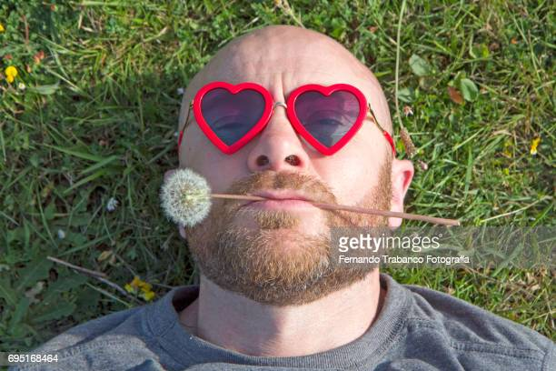 Man with heart shaped sunglasses and dandelion in his mouth