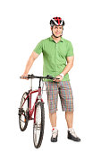 Full length portrait of a man with a helmet pushing a bike isolated on white background