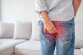 Man hand holding his bottom because having Abdominal pain and Hemorrhoids, Health care concept. Man with hemorrhoids and constipation.