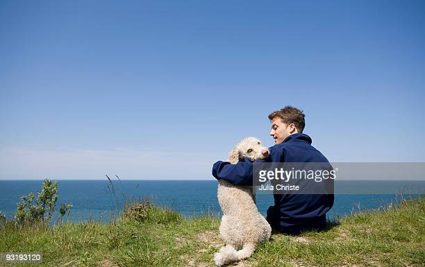 A man with his arm around a dog sitting by the sea