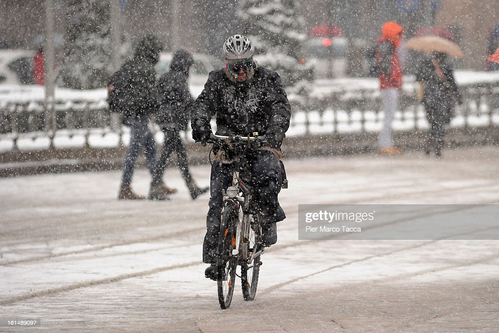 A man with his bicycle in heavy snow on February 11, 2013 in Milan, Italy.Wind, snow and tempetarture under zero over the country has affected regions from North Italy to South Italy, transports has been affected with train cancellations and road closures.