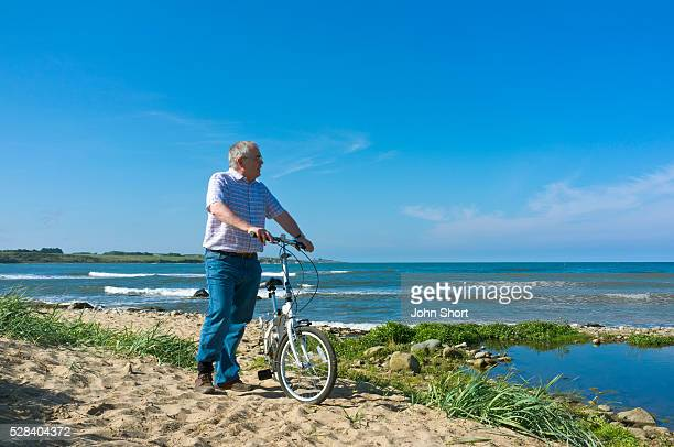A Man With His Bicycle On The Beach Along The Coast; Northumberland England