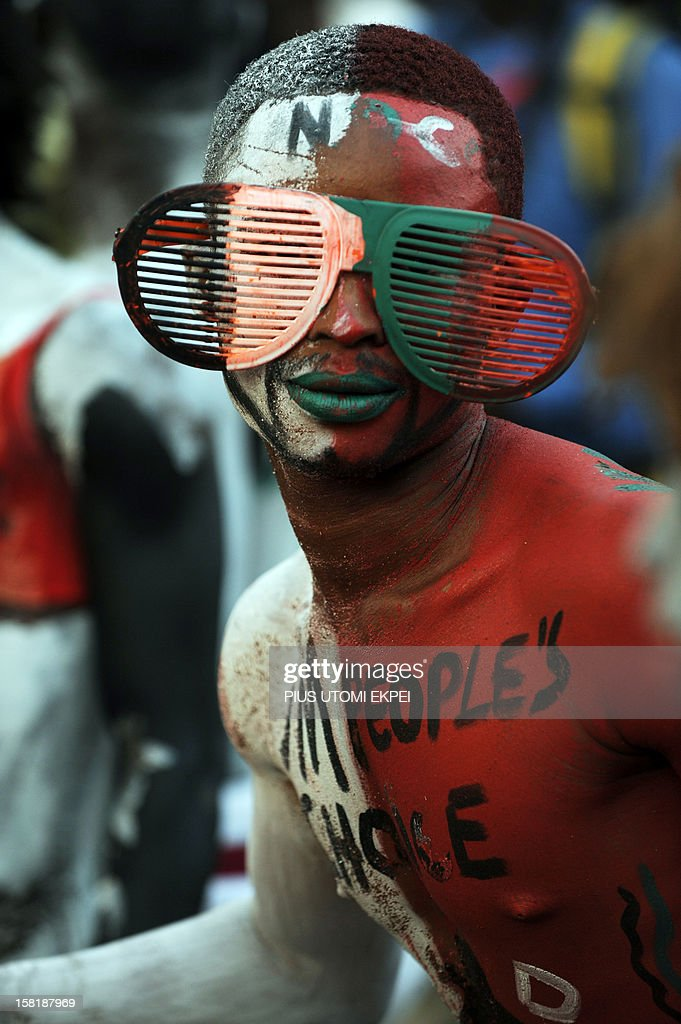 A man with his body painted in Ghanaian ruling National Democratic Congress party colors attends a rally at Kwame Nkrumah Circle in Accra on December...