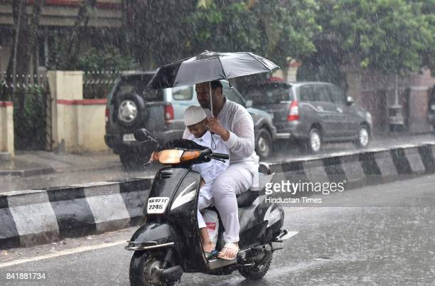 A man with his child on his way to offer prayer amid heavy rain on the occasion of Eid alAdha the festival of sacrifice at MasjideKhadira on...
