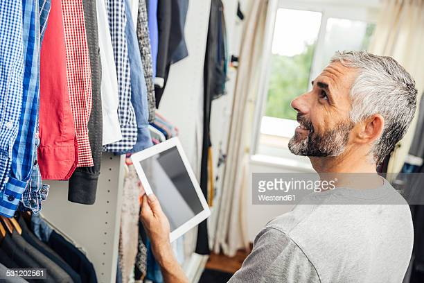 Man with his digital tablet standing at his walk-in closet