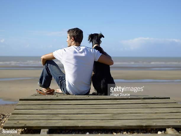 Mann mit seinem Hund am Strand