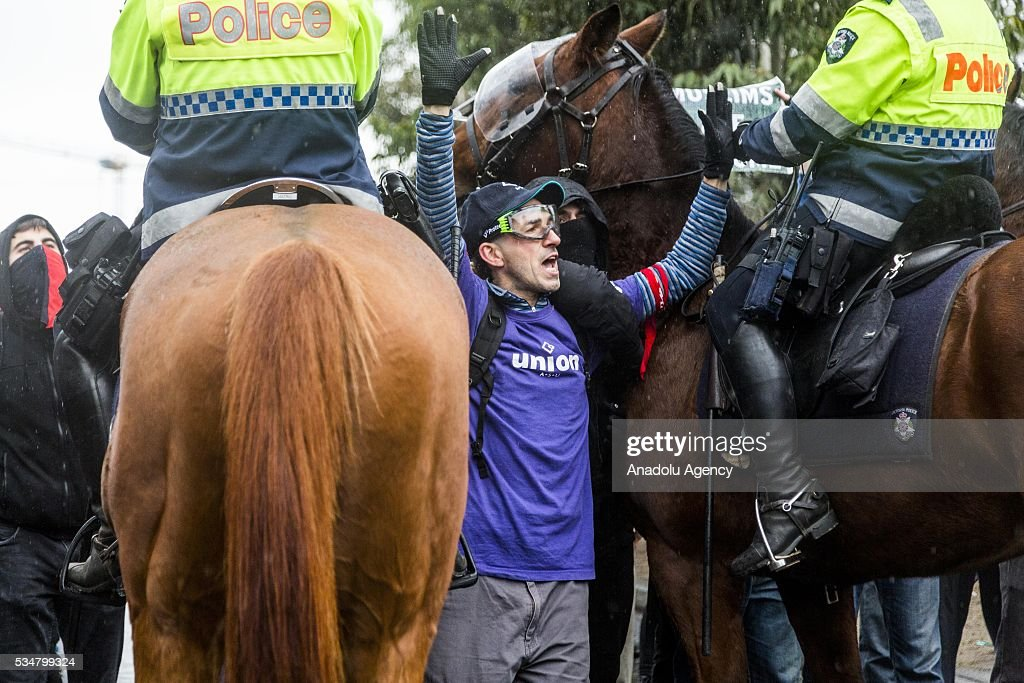 A man with his hands up stands between two police horses during a 'Say No To Racism' protest and a counter 'Stop the Far Left' rally in Coburg Melbourne, Australia on May 28, 2016. Seven men were arrested after a violent brawl erupted between rival protesters at an anti-racism rally in Melbourne's inner-north. Anti-Facists clashed with Anti-Islam nationalists who go by the name 'True Blue Crew'.