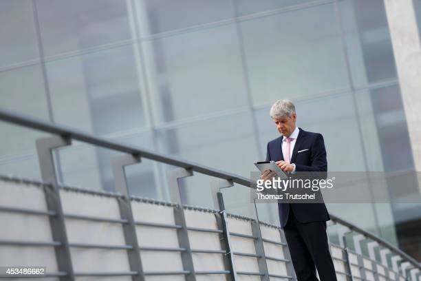 Man with his iPad wearing a business suit crosses a brigde on August 07 2014 in Berlin Germany