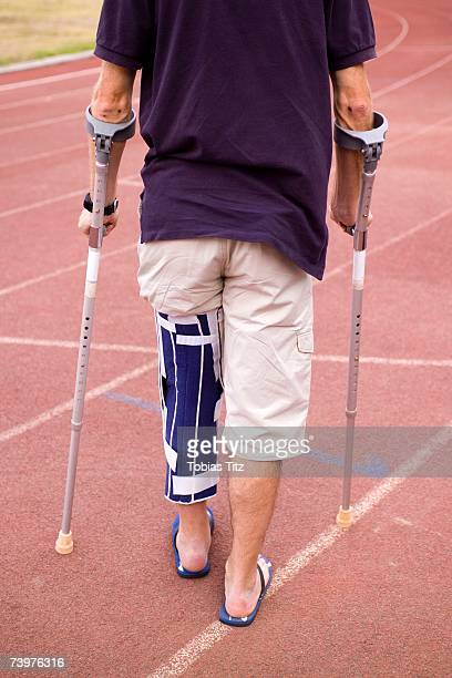 Man with his leg in a brace and using crutches