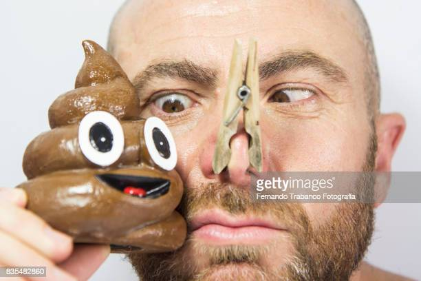 Man with his nose covered to not smell the poop