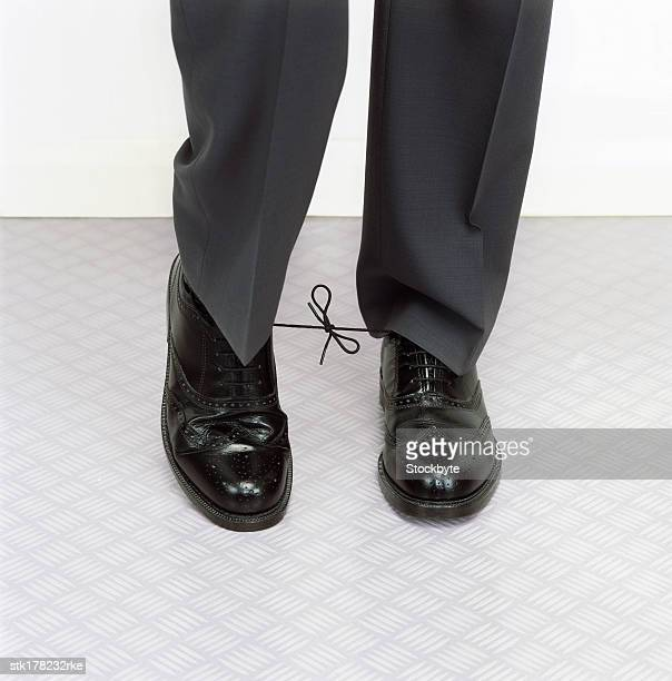 man with his shoe laces tied together