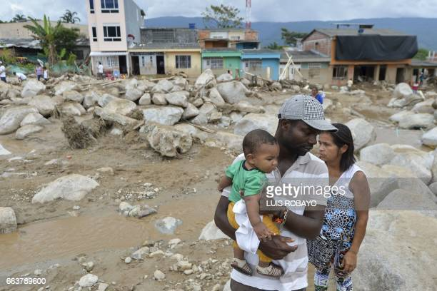 A man with his son looks at damages caused by mudslides following heavy rains in Mocoa Putumayo department southern Colombia on April 2 2017 The...