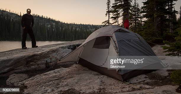 Man with his tent at dusk.