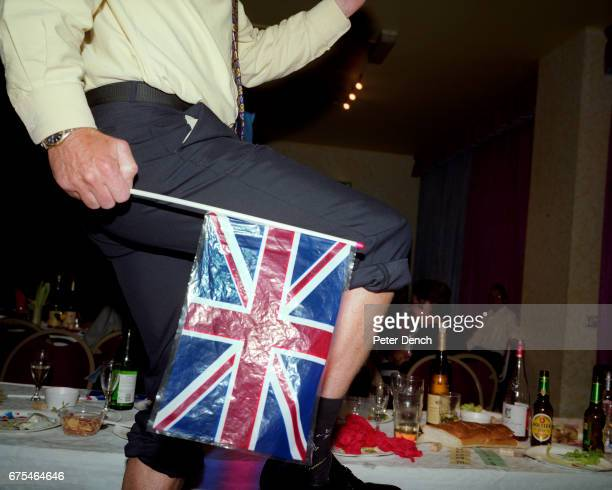 A man with his trousers rolled up and shoes removed dances on a table in his socks at an Oktoberfestthemed evening hosted at the Weymouth Pavilion...