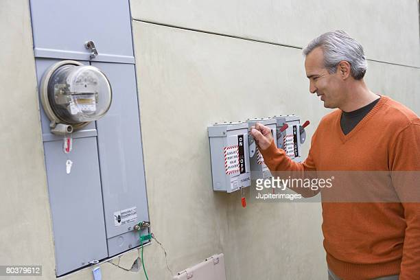 Man with home electric meter and circuit breakers