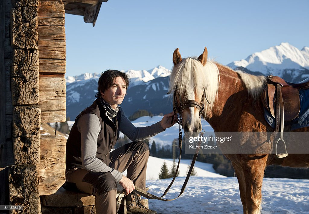 man with horse in winter mountain scenery : Stock Photo
