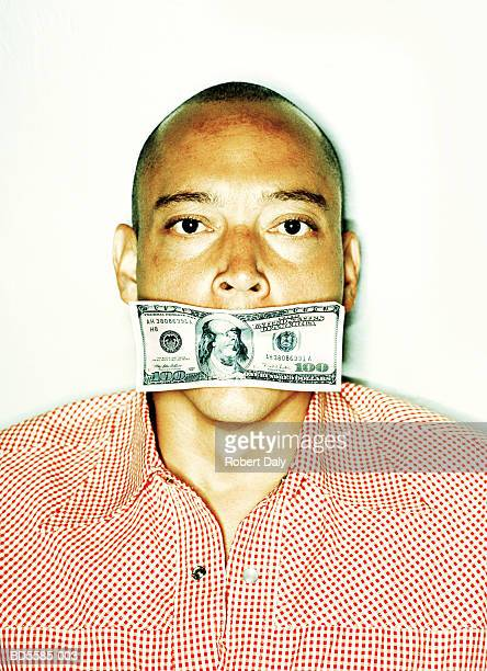 Man with hundred dollar bill in mouth, close-up, portrait