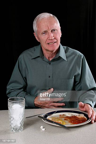 Man with indigestion after meal. Pushing away plate. Dinner table.