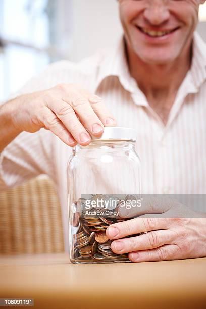 man with jar of cash